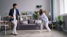 Canto ballante della giovane famiglia durante il lavoro domestico facendo uso dell'aspirapolvere a casa archivi video