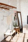 Canto da sala do projeto do sótão com as paredes de tijolo brancas, flores no potenciômetro do ferro, espelho, treinador Conceito Foto de Stock