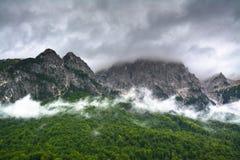 Canto de la montaña en las nubes y bosque en la cuesta foto de archivo