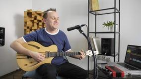 Canto del musicista e chitarra elettrica di gioco nello studio domestico di musica stock footage