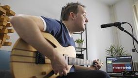Canto del musicista e chitarra elettrica di gioco nello studio domestico di musica video d archivio