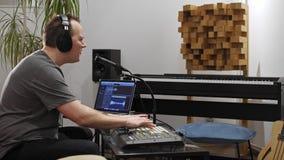 Canto del musicista e giocare la tastiera del Midi nello studio domestico di musica video d archivio