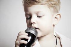 Canto del ragazzino in microphone.child in karaoke.music Immagine Stock