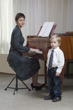 Canto del ragazzo come insegnante Play The Piano Fotografia Stock Libera da Diritti