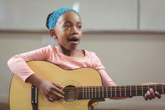 Canto dell'allievo e chitarra svegli di gioco in un'aula Immagine Stock Libera da Diritti