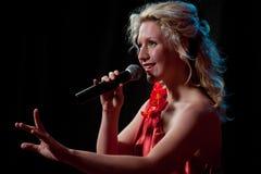 Canto della donna in microfono Fotografie Stock Libere da Diritti