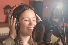 Canto della ragazza con un microfono e le cuffie fotografia stock libera da diritti