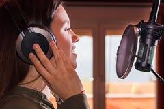Canto della ragazza con un microfono e le cuffie immagine stock