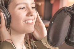 Canto della ragazza con un microfono e le cuffie fotografie stock