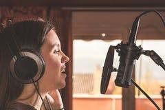 Canto della ragazza con un microfono e le cuffie immagine stock libera da diritti
