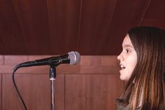 Canto della ragazza con un microfono in uno studio di musica fotografie stock libere da diritti