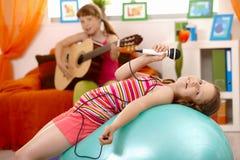 Canto della ragazza, proponente sulla sfera di ginnastica Immagini Stock