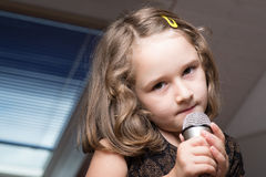 Canto della ragazza su un microfono Fotografia Stock Libera da Diritti