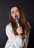 Canto della ragazza in un microfono Fotografie Stock Libere da Diritti