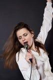 Canto della ragazza in un microfono Immagine Stock