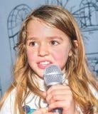 Canto di nove anni della ragazza con il microfono Immagini Stock