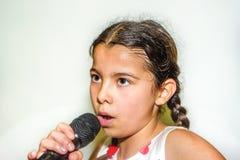 Canto di nove anni della ragazza con il microfono Fotografie Stock Libere da Diritti