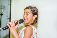 Canto di nove anni della ragazza con il microfono Fotografia Stock Libera da Diritti