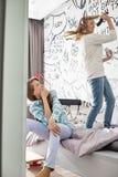 Canto di sorveglianza della sorella della ragazza nella spazzola per i capelli in camera da letto Fotografie Stock Libere da Diritti
