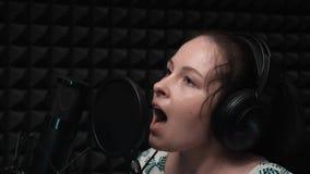 Canto emozionale Bella donna caucasica che canta nello studio di registrazione Studio di musica vocale con il microfono ed il fon archivi video