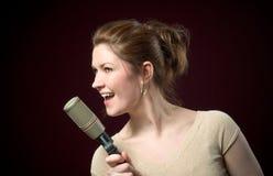 Canto modelo del Redhead hermoso en el micrófono imágenes de archivo libres de regalías