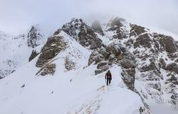 Canto nevoso ascendente de la montaña del escalador fotos de archivo