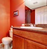 Canto vermelho do banheiro com um armário da bacia Foto de Stock