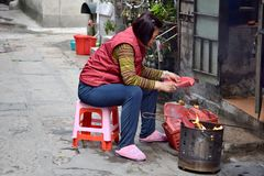 CANTON, CHINA – CIRCA FEBRUARY 2018:  A woman offers a sacrifice during the Chinese New Year. A woman offers a sacrifice during the Chinese New Year in front Royalty Free Stock Photography