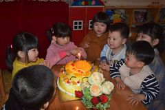 CANTON, CHINA – CIRCA MARCH 2019: Group of kids in kindergarten sitting around a birthday cake to celebrate a birthday. stock photo