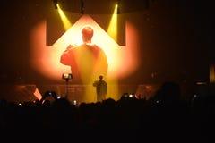 Cantor Back Turned à audiência e à câmera, fase do concerto da música, projetores coloridos, multidão, fãs Fotografia de Stock
