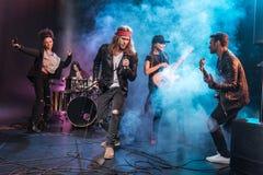 Cantor com a faixa de rock and roll que executa a música na fase foto de stock royalty free