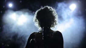 Cantor fêmea backlit na fase fumarento filme