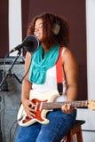 Cantor fêmea With Eyes Closed que joga a guitarra elétrica fotografia de stock