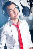 Cantor masculino asiático produzindo a música no estúdio de gravação Imagem de Stock
