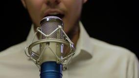 Cantor masculino caucasiano novo que executa no estúdio com o microfone video estoque