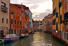 Cantos coloridos de Veneza no por do sol com construções velhas e arquitetura, nos barcos e em reflexões bonitas da água, Itália imagem de stock