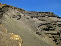 Cantos en los acantilados en la playa verde de la arena, Hawaii fotografía de archivo libre de regalías