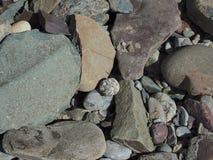 Cantos rodados de río enormes de la forma angular de diversos tamaños, en la piedra verde grande derecha Foto de archivo libre de regalías