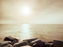 Cantos rodados mojados grandes en orilla en el mar ondulado liso Desafios pedregosos de la costa a las ondas Fotos de archivo libres de regalías