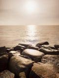 Cantos rodados mojados grandes en orilla en el mar ondulado liso Desafios pedregosos de la costa a las ondas Fotos de archivo