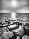 Cantos rodados mojados grandes en orilla en el mar ondulado liso Desafios pedregosos de la costa a las ondas Foto de archivo libre de regalías
