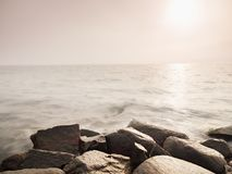 Cantos rodados mojados grandes en orilla en el mar ondulado liso Desafios pedregosos de la costa a las ondas Foto de archivo