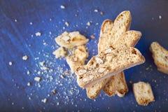 Cantucci - biscotti italiani con le mandorle su un fondo blu con le briciole sistemate in una piramide fotografie stock libere da diritti