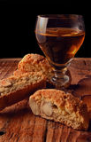 Cantucci and vino santo. A glass of Tuscan vino santo wine surrounded by tuscan cantucci almond cookies on a rustic wooden board Royalty Free Stock Images