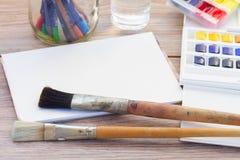 Canva branco com quadro das pinturas e das escovas imagem de stock