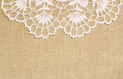 Canvas background with crochet lace. Canvas background with white crochet lace on the top Stock Photo
