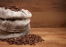 Canvas bag with coffee beens. On rustic table with wooden texture Stock Image