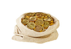 Canvas bag filled with coins. A white background. Royalty Free Stock Image