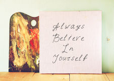 Canvas board with the phrase always believe in yourself, over wooden background Royalty Free Stock Images