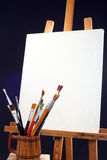 Canvas, brushes and easel Stock Photos